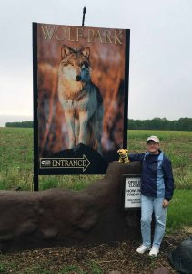 person in front of sign for Wolf Park