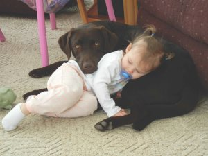 baby cuddled against a young pup